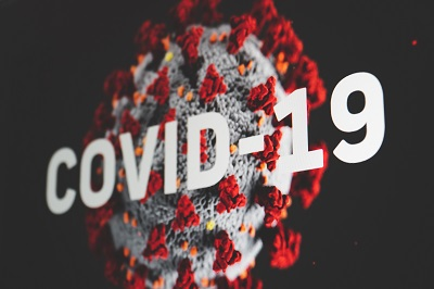 COVID-19 in white text with image of virus in background